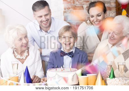 Happy boy surrounded by family at his birthday party