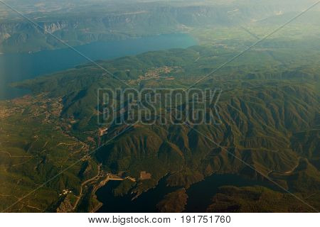 A picturesque landscape with rocky mountains, overgrown with dense green trees