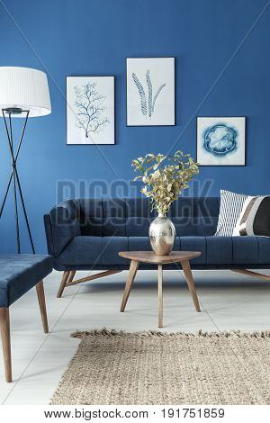 Stylish end table with flower vase and vintage sofa in cyan living room