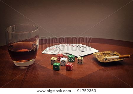 Glass of alcohol, cards, dice and ashtray with cigarette on the brown table. Filtered photo with toned and selective focus on dice.