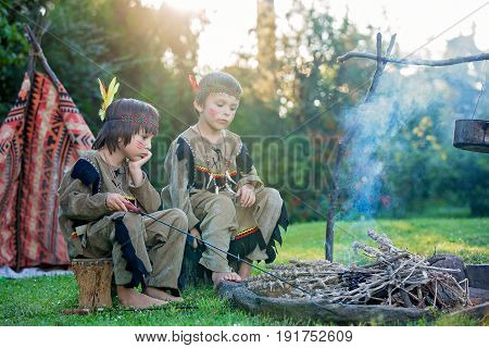 Cute Portrait Of Native American Boys With Costumes, Playing Outdoor Around Fire On Sunset