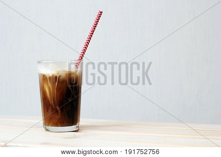 a glass of cold coffee with ice cream with a cocktail straw on a table against white wall copy space