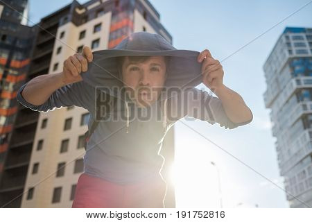 Mature man looking down, walking on street. He hide his face with hood