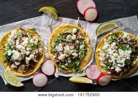 three mexican carne asada beef tacos with queso fresco cheese in flat lay composition