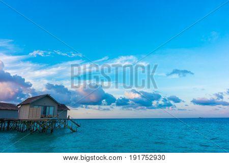 Beautiful sunrise with  water villas  in tropical Maldives island