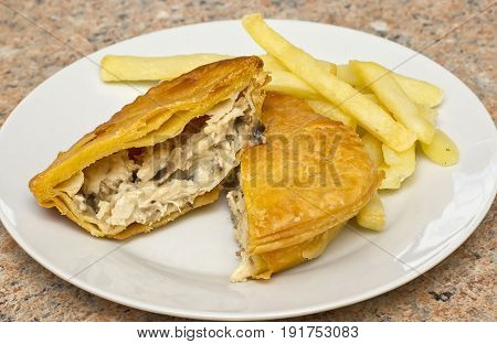 Chicken and mushroom pie on a white plate with some fries on the side
