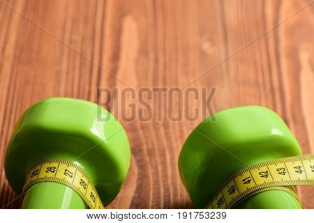 Sport Equipment And Workout Concept With Dumbbells And Measuring Tape