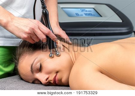 Close up of young woman receiving electrotherapy on face.Therapist stimulating nerves and muscles on cheek.