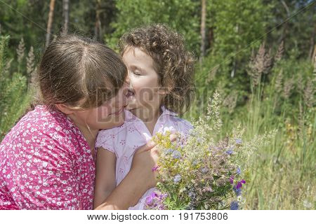 In summer on a bright sunny day on the lawn Mom holds a bouquet of wildflowers and kisses a small curly daughter.