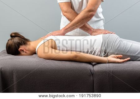 Close up of male physiotherapist doing manipulative massage on young woman.