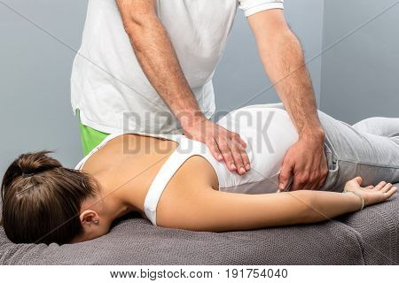 Close up of male osteopath doing manipulative massage on female lower back.
