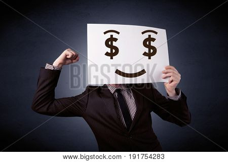 Young casual businessman hiding behind a greedy face drawing on cardboard