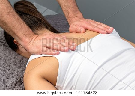 Close up detail of therapist applying pressure with hands on female shoulder.