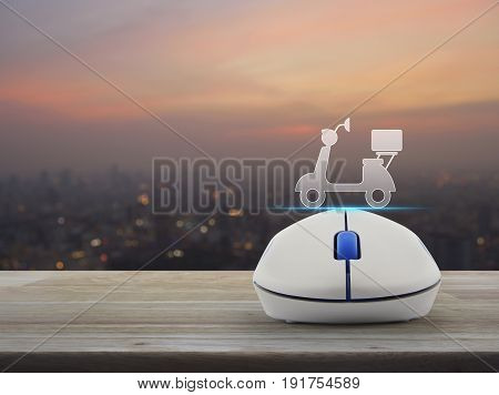 Motor bike icon with wireless computer mouse on wooden table over blur of cityscape on warm light sundown Business internet delivery service concept