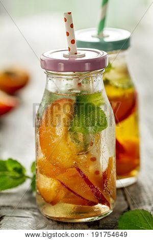 Healthy tasty fresh refreshing detox water in bottles or jars with apricots mint and ice on wooden background. Closeup. Healthy Life Concept.