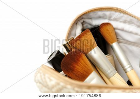 Open cosmetic bag with makeup brushes and a set of cosmetics. Isolated on white