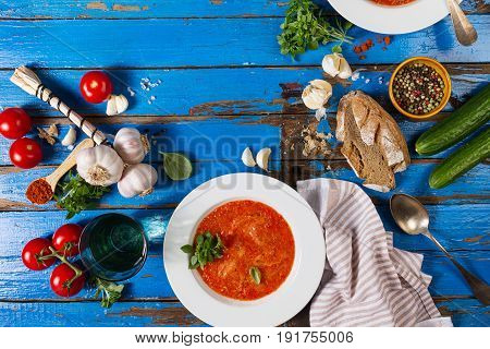 Tasty appetizing classic spanish soup gazpacho in white plates on rustic blue table with bread garlic and spices. Dinner Food Concept. Top View.