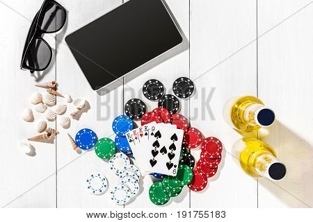 Poker. Set to playing poker with cards and chips on white wooden table, top view. Copy space