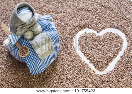 Buckwheat background with a handmade textile doll. Heart made with buckwheat. Close up