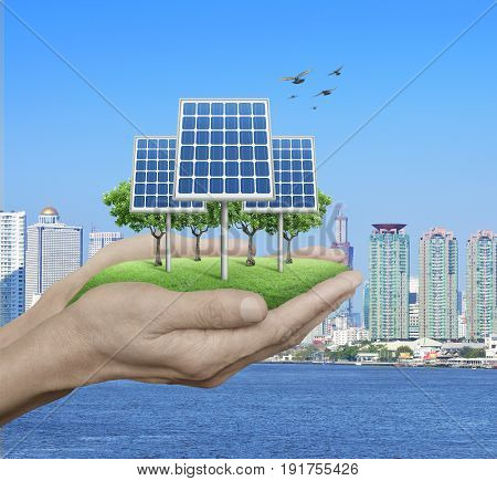 Solar cell in man hands over city tower and river with birds Ecological concept