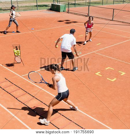 Cardio tennis training outdoors, summer time, color image