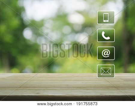 Telephone mobile phone at and email buttons on wooden table over blur green tree background Customer support concept