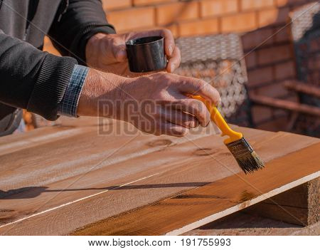 Brushing wood with brush. Painting and wood maintenance oil-wax. Maintaining of wooden surfaces with fresh protective paint.