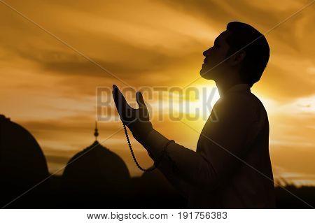 Silhouette Of Asian Muslim Man Raising Hand And Praying