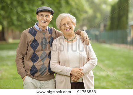 Senior couple in the park looking at the camera and smiling
