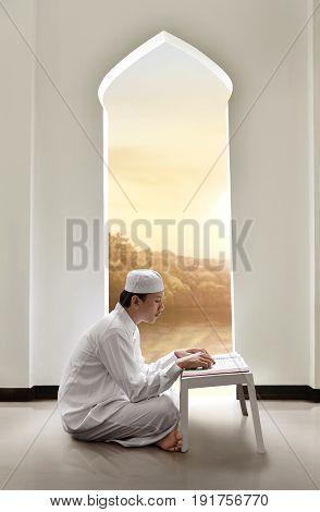 Young Asian Muslim Man With Cap Reading Holy Book Koran