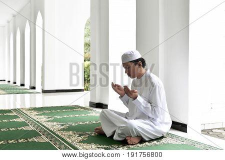 Portrait Of Asian Muslim Man Raising Hand And Praying