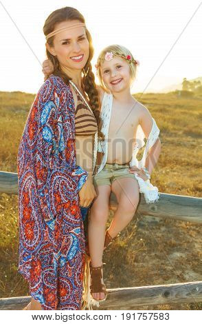 Mother And Child Outdoors In Summer Evening Sitting On Fence