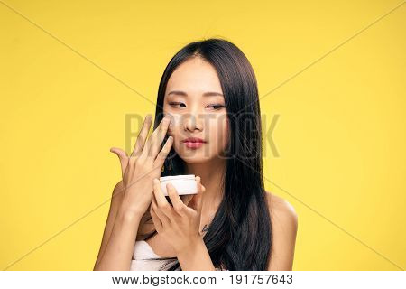 Woman applying cream, facial, woman on yellow background.