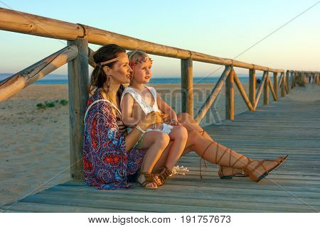 Mother And Daughter Sitting Near Fence Looking Into The Distance