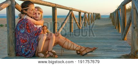 Boho Mother And Child Outdoors In Summer Evening Hugging
