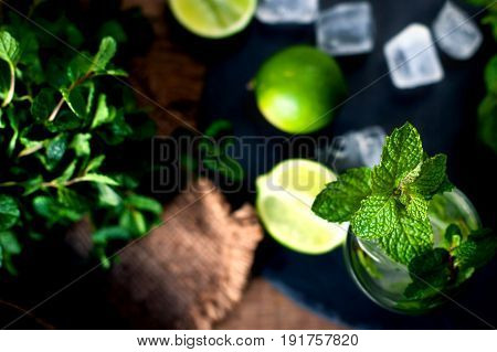 Ingredients for mojito lime mint leaves ice. Cold drink glass on a black stone background Copyspace