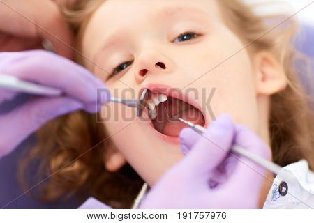 Hands of unrecognizable pediatric dentist holding lip up and making examination of cute little girl lying with mouth opened in chair in a clinic.
