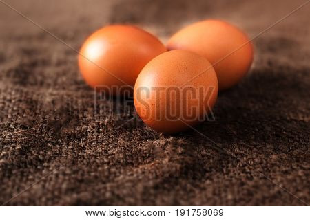 Heap of fresh brown Eggs on wooden background closeup image in dark orange colors