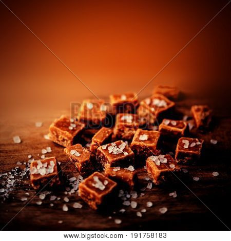 Toffees. Caramel pieces with copy space for your design over dark orange wooden background.