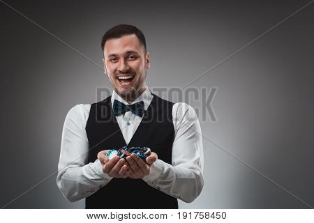 A man holding up poker chips. Man in shirt and butterfly in studio on gray background. Poker