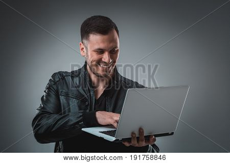 Man in black jacket looking at laptop, half turn. Holding opened laptop and working. Emotion. Indoors, studio, waist up, profile