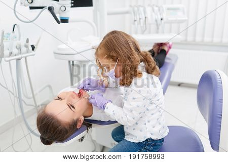 Adorable little girl sitting and making an examination of woman doctor lying on dentist chair in hospital. Dentist and child in cabinet. Dentist office. Little girl in the dentists office