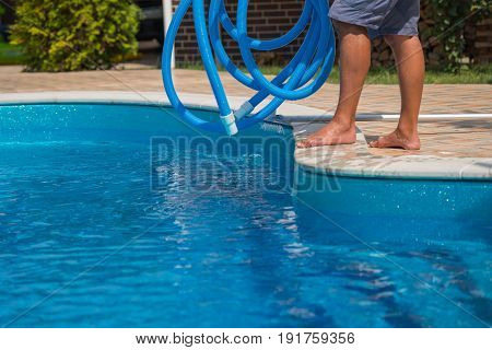 Man cleaning the swimming pool with blue hose, service, closeup