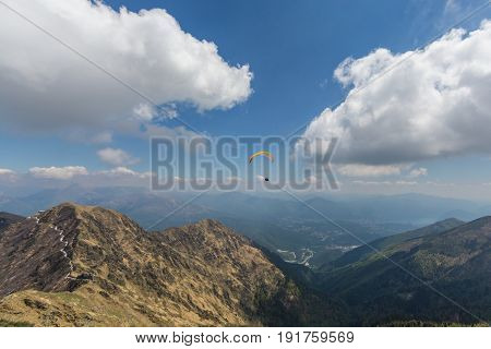 paragliding in the Swiss mountains with blue sky and clouds with sunshine