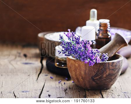 Lavender spa bunch of lavender flowers essential oil and salt on a rustic wooden background.