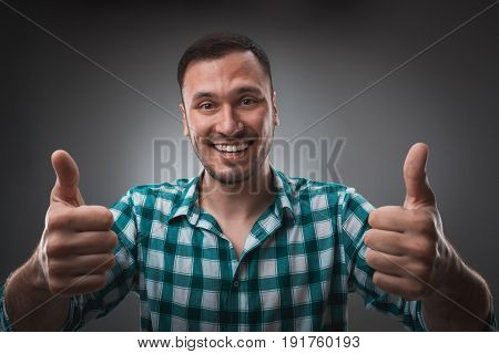 Portrait of excited happy man showing thumb up sign and smiling. Isolated on gray background. Emotion concept