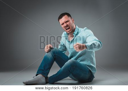 The man is sitting on the floor, isolated on gray background. Man showing different emotions. A man is dressed in blue jeans and a shirt