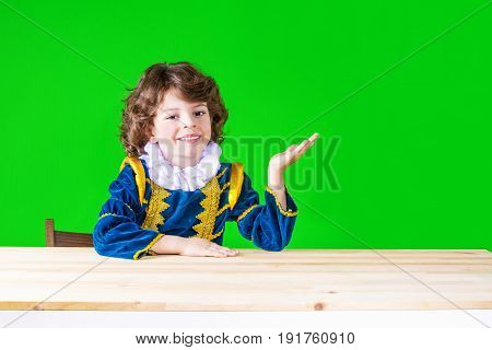 Happy Curly-haired Boy In Prince Clothes Holding Up A Hand, Palm Up, Looking Into The Camera. Close-