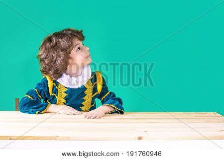 Cute Curly-haired Boy In The Clothes Of Prince Put His Hand On The Table Turned His Head To The Left