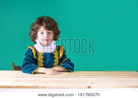 Cute Curly-haired Boy In The Clothes Of Prince Put His Hand On The Table Looking At The Camera. Clos